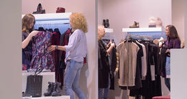 Women shopping at clothing store HD video. Female shoppers look for wear hangers Footage