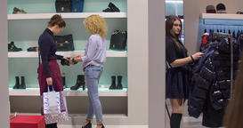 Women shopping at clothing and footwear store HD video. Female choose shoes Footage