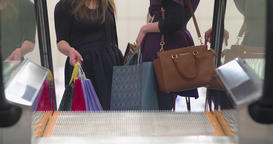 Women friends shopping at mall HD video. Girls with sale boxes moving escalator Footage