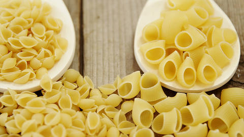 Various pasta in spoons on wooden background and also scattered on wooden Footage