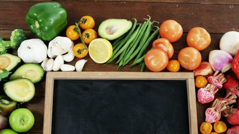 Chalkboard surrounded with fresh vegetables and fruits on... Stock Video Footage