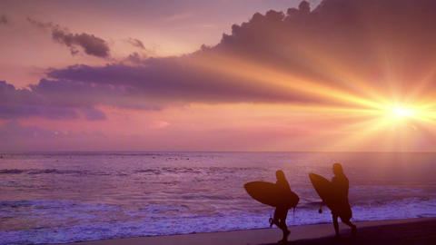 Surfers carrying surfboards walk along shoreline washed by ocean waves. Bali Footage