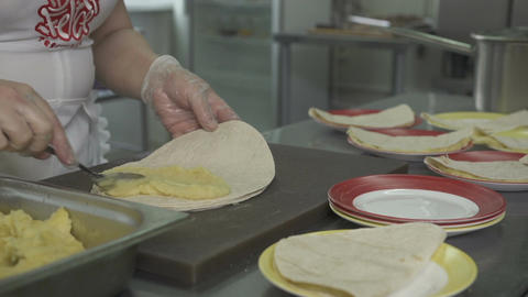 Woman Wraps Mashed Potatoes in Pita Bread and Puts on Plates Footage