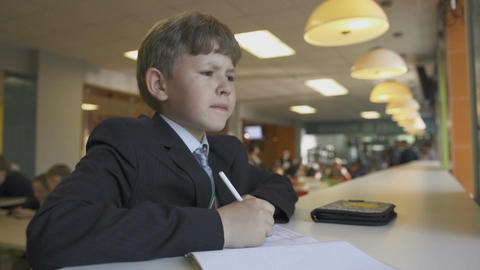 Schoolboy Sits and Writes Something with Pen in Notebook Filmmaterial