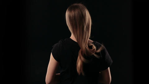 Back view woman letting down blond straight hair Live Action