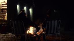 Young couple sitting front of bonfire Footage