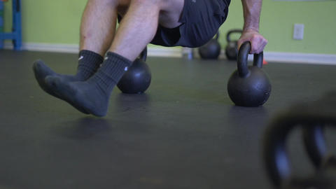 Man walks over to kettle bells and starts working out Footage