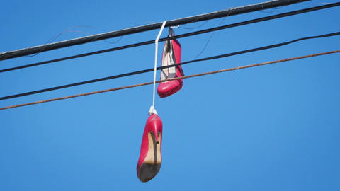 Three videos of pair of stilettos hang tossed on telephone wire in 4K Footage