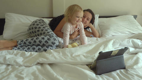 Mother and daughter watching cartoons on tablet computer Live Action