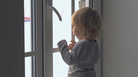 Little baby girl standing near the window and looking outside Footage