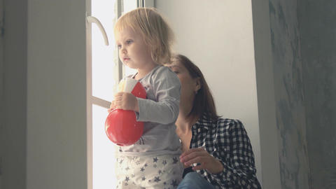 Mother with her little baby girl standing near the window and looking outside Footage