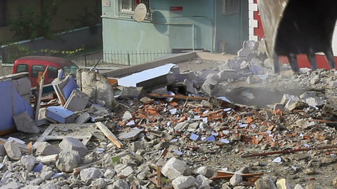 Excavator turns old homes into rubble and dust fills the air Footage