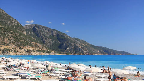 Oludeniz Beach with tourists, sunbeds and umbrellas. Mediterranean beach with tu Footage
