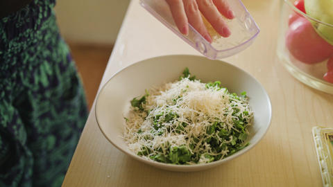 Woman Sprinkles Cheese on Salad Footage