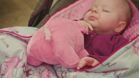 Sleeping Baby with Toy in a Car Seat Filmmaterial