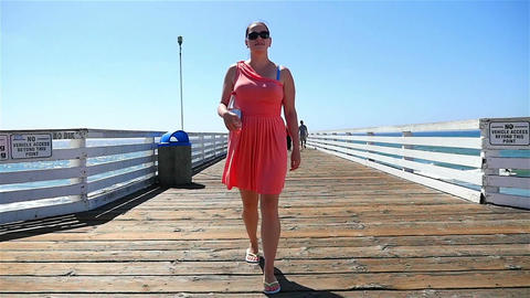 Two videos of woman at the pier in California in slow motion Footage