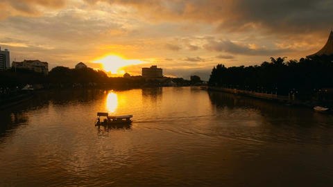 Sarawak River dyed in sunset, a shot across which a boat crosses Footage