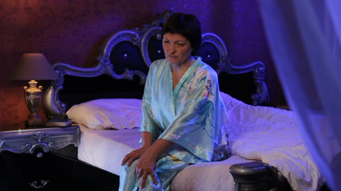 Tired Woman in Silk Bathrobe Sits on Bed Edge and Massages Knee Footage
