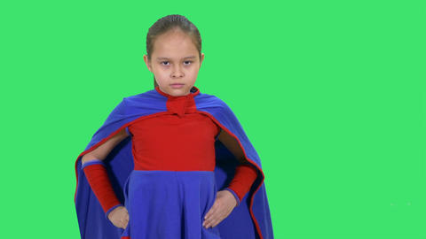 Young girl superhero standing on greenscreen hands on hips looks serious Footage