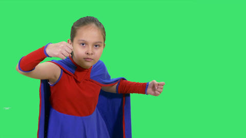 Young girl superhero standing on greenscreen in fighting pose Footage