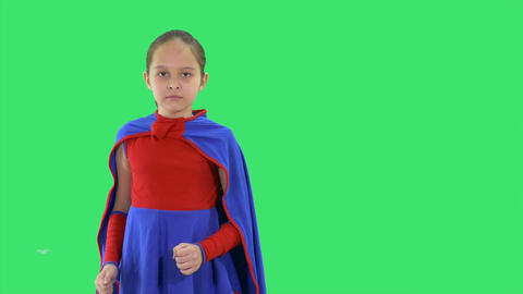 Young girl superhero standing on greenscreen moves into fight stance Footage