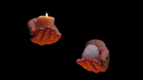 candle fire and ice in balancing hands on black background - philosophical abstr Footage
