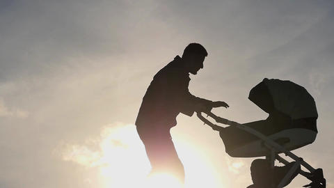 man with baby carriage entertain and care of the child silhouette 2 Footage