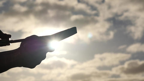 manual knife sharpening closeup silhouette with clouds and sunshine Footage