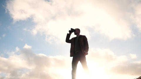 man with binoculars against sun view slow motion 2 Filmmaterial