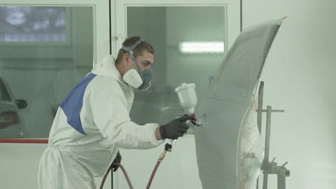 Worker in Respirator Paints Car Door with Sprayer Live Action