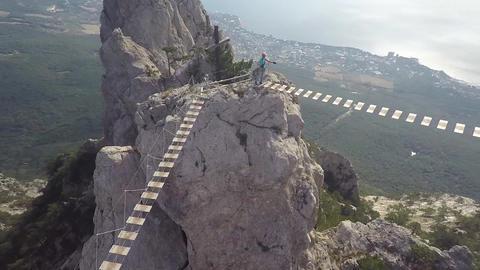 Apic aerial shot of man walking suspension bridge to Cross in Crimea. High rocks ビデオ