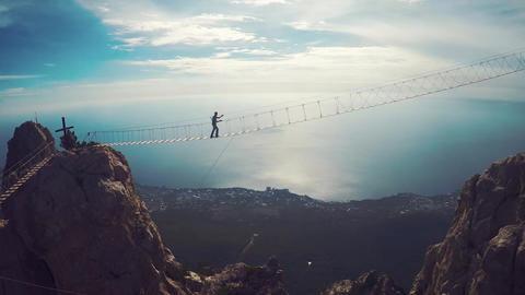 Apic aerial shot of man walking suspension bridge to Cross in Crimea. High rocks