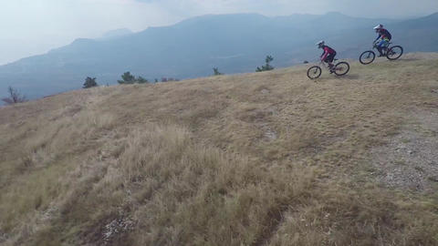 Epic aerial view of mountain bikers ride on mountain in the fog. Cloudy sky, aut