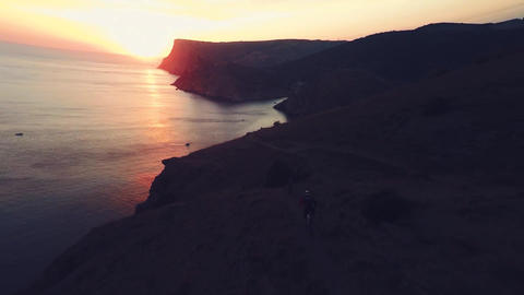 Aerial of sunset. Timelapse sunrise in the mountains. Bike riders. Sea coast. Ca Footage