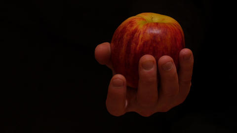 isolated hand with apple moves on black background, can be applied for Original  Live Action
