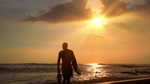Surfer holding surfboard and passing by on sand beach washed by sea waves. Bali Footage