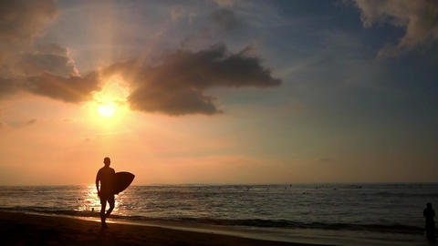 Silhouettes of surfers at evening tropical beach. Perfect vacation at Bali Footage