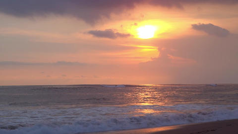 White crested ocean waves illuminated by orange setting sun break on sand shore Footage