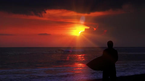 Figure of man walking along surf line and carrying surfboard against sunset sky Footage