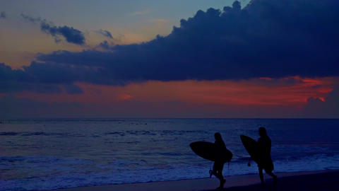 Silhouettes of surfers holding surfboards and walking along surf line. Bali Footage