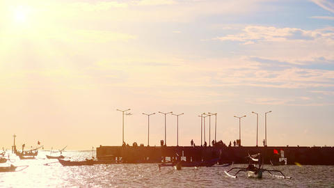 Silhouettes of people walking along pier surrounded by outrigger fishing boats Footage