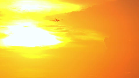 Silhouette of flying airplane in orange sunset sky. Descending aircraft Footage