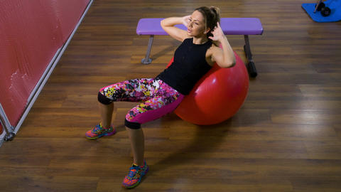 Attractive slender woman doing sports exercise using fitness ball at the gym Footage