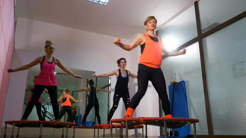 Middle age women doing exercises at the gym using mini trampoline Footage