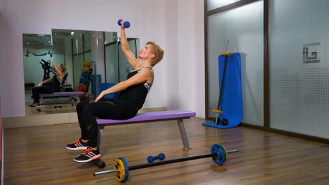 Woman training at the gym on bench with dumbbells Footage