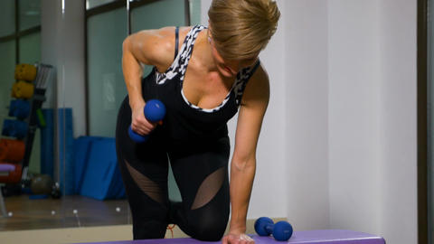 Strong woman lifting dumbbells at fitness club Footage