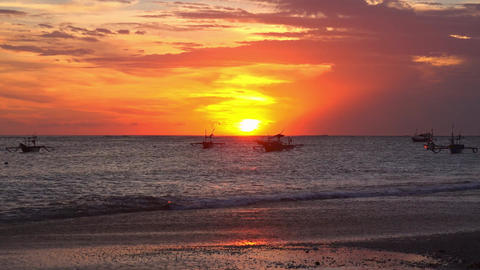Orange sunset sky, silhouettes of fisherman's boats floating in ocean Footage