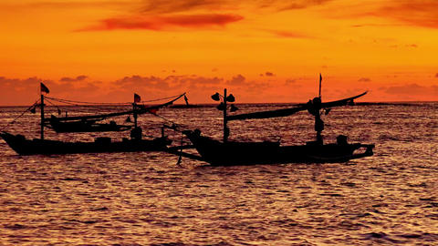 Silhouettes of traditional fishing vessels floating in ocean against sunset sky Footage