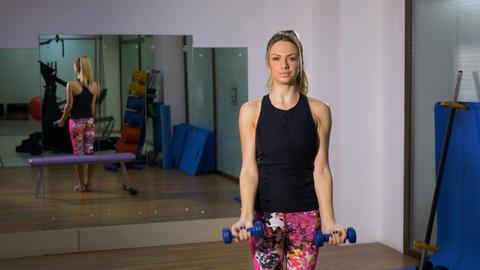 Young woman exercising with dumbbells at the gym looking at camera Footage