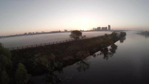 Scenic aerial of the fog clouds towards the sun on the field and river. Thick fo Footage